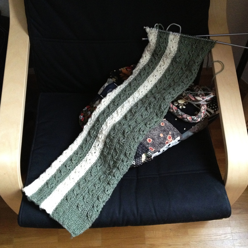 Partially knitted scarf with knitting needles and yarn