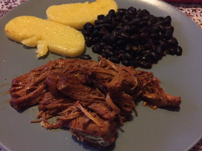 Plate with cochinita pibil, polenta, and black beans